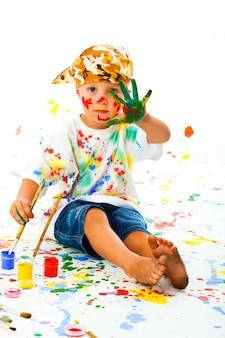 Petit garçon taché de peinture dessine