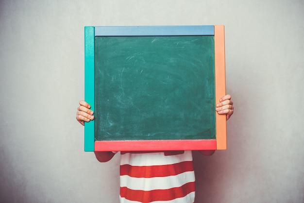Petit garçon tenant la bannière du conseil vert de l'école devant sa tête