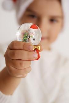Petit garçon tenant une boule de neige de noël sur fond blanc. enfant heureux, fête de noël, temps de noël.