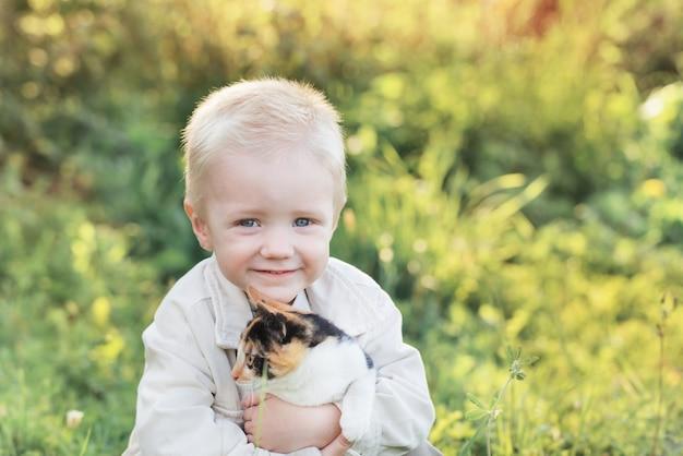 Petit garçon tenant le chaton le jour d'été ensoleillé