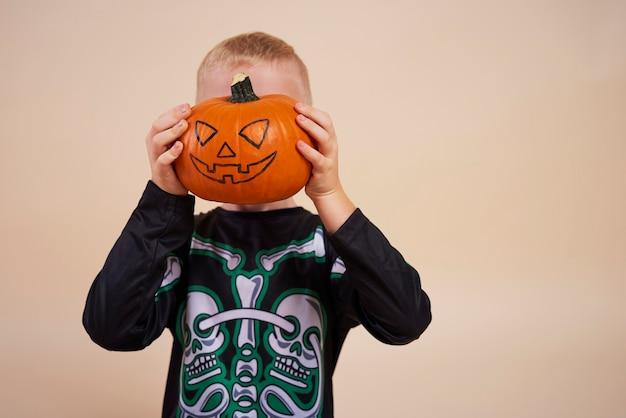 Petit garçon tenant la citrouille d'halloween devant son visage