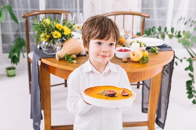 Petit garçon tenant la tarte dans les mains