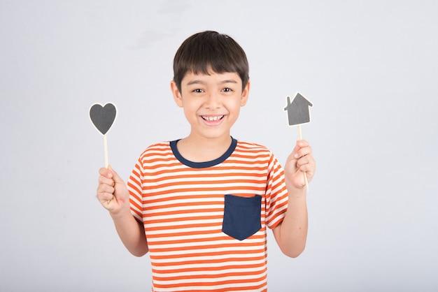 Petit garçon, tenue, enseigne, maison, et, coeur