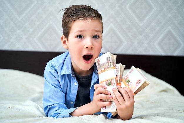 Un petit garçon tient des billets de cinq mille dollars dans ses mains au-dessus d'un lit