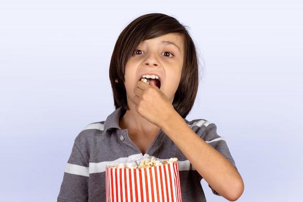 Petit garçon en train de manger du maïs soufflé.