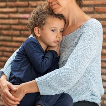 Petit garçon triste réconforté par sa mère