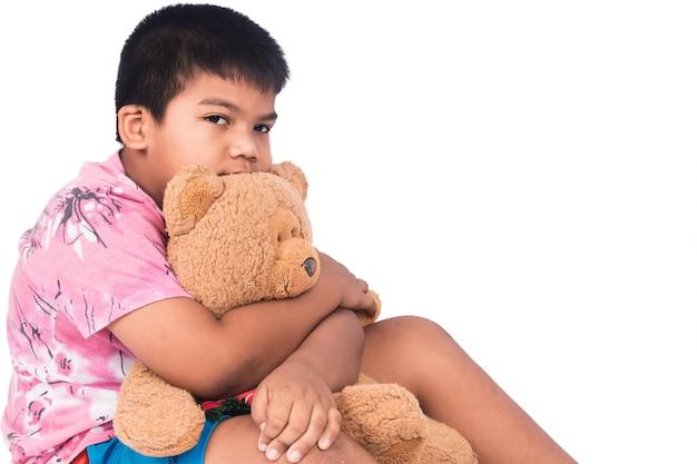 Petit garçon triste seul avec ours en peluche brun