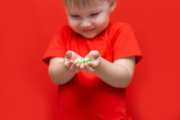 Petit garçon triste tenant beaucoup de pilules dans les mains