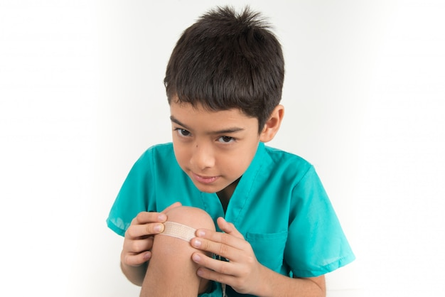 Petit garçon, utilisation, bande plâtre, bâton, genou