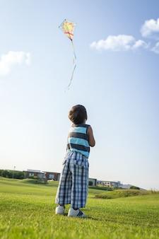 Petit garçon sur les vacances d'été s'amuser et heureux temps voler cerf-volant sur la plage de la mer