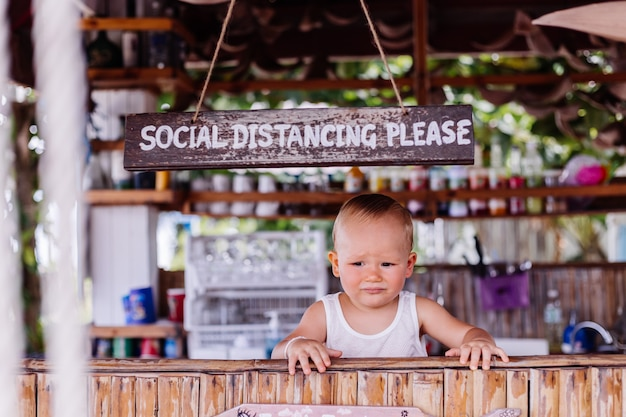 Petit garçon en vacances en thaïlande avec signe de distance sociale au bar
