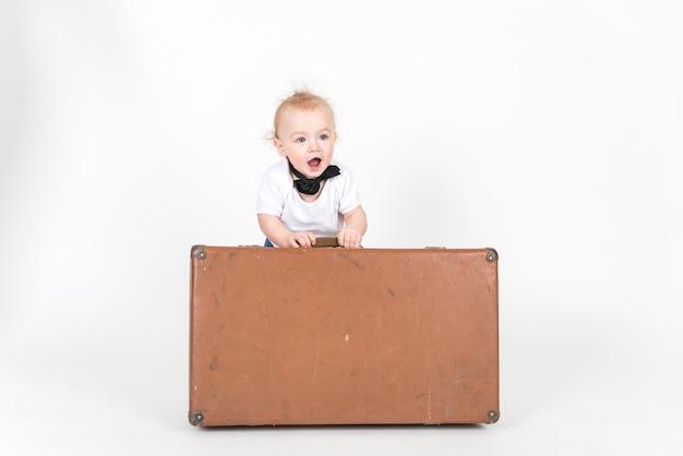 Petit garçon avec la valise sur l'espace blanc