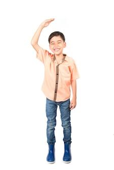 Petit garçon vérifiant sa taille sur blanc