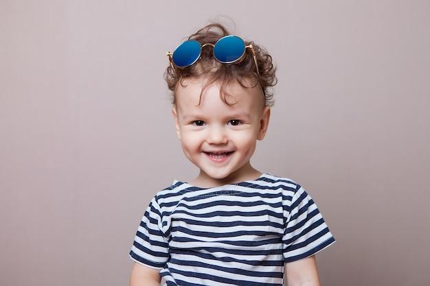 Petit garçon en veste souriant. fond gris, studio