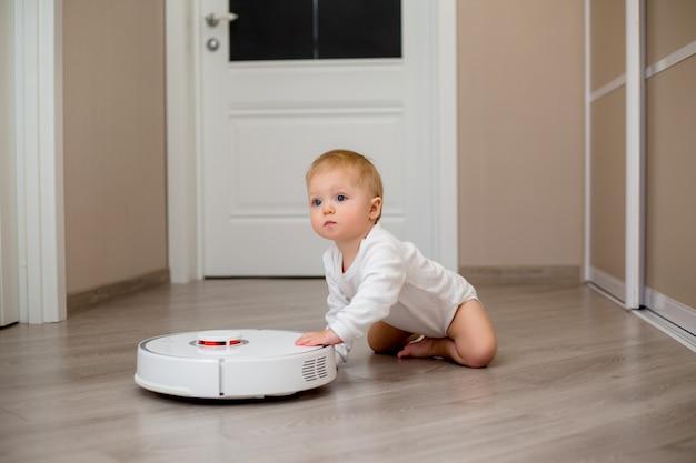 Petit garçon en vêtements blancs avec un aspirateur robot sur le sol de la maison
