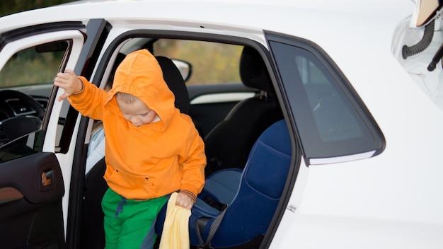 Petit garçon vêtu d'un haut à capuche orange coloré et d'un pantalon vert sortant de la porte arrière d'une voiture