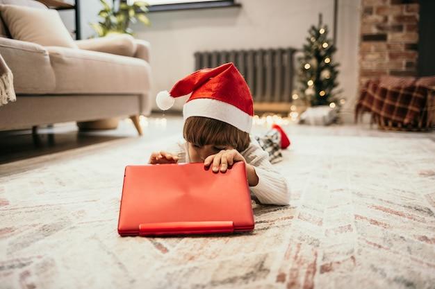Un petit garçon vêtu d'un pull blanc et d'un chapeau de noël rouge se trouve sur le tapis de la pièce et ouvre un ordinateur portable