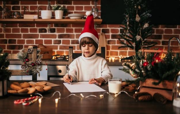 Un petit garçon vêtu d'un pull blanc et d'un chapeau rouge est assis à une table et écrit une lettre du nouvel an