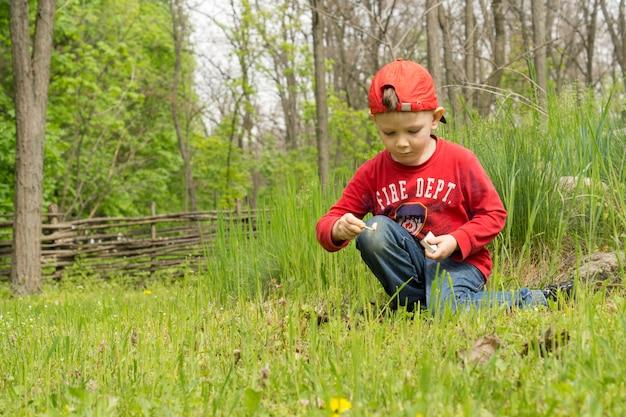 Petit Garçon Vêtu D'un Pull Rouge Des Pompiers S'agenouillant Dans L'herbe Verte Allumant Son Propre Petit Feu De Camp Photo Premium