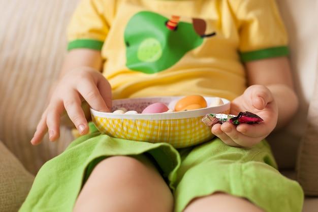 Un petit garçon vêtu d'un t-shirt jaune et d'un short vert assis et mangeant des œufs en chocolat de pâques