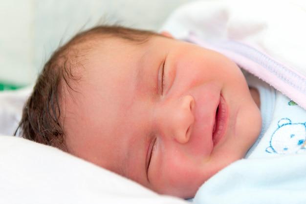 Un petit garçon avec un visage souriant pendant le sommeil
