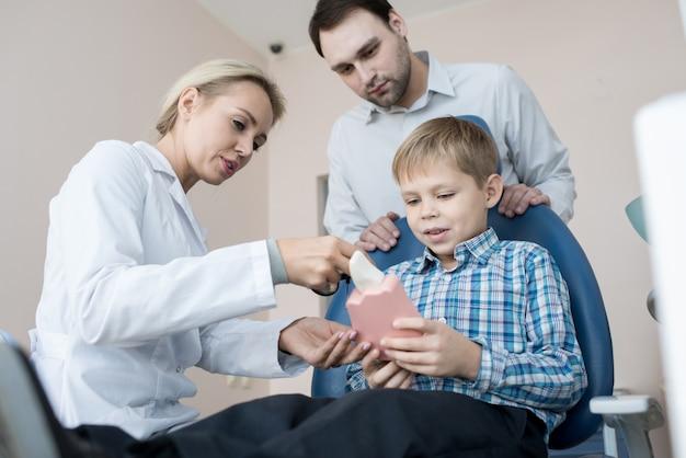 Petit garçon visite dentiste avec papa