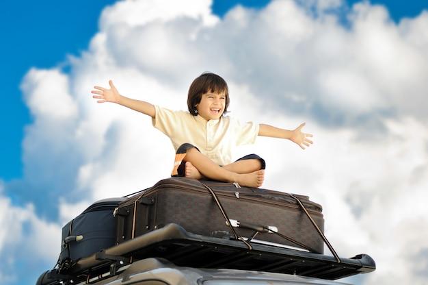 Petit garçon voyageant sur le toit de la voiture