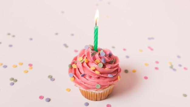 Petit gâteau d'anniversaire rose avec une bougie allumée