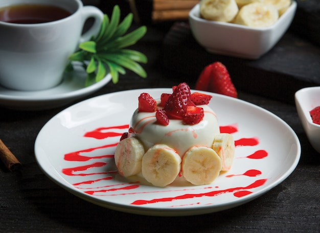 Petit gâteau au chocolat blanc avec des bananes et des fraises