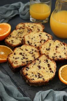 Petit gâteau aux oranges et au chocolat, situé sur un support en ardoise sur un fond sombre