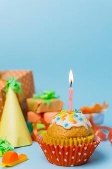 Petit gâteau avec une bougie allumée et un arrangement d'anniversaire derrière lui