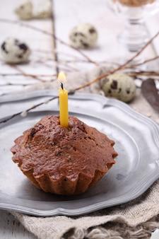 Petit gâteau avec une bougie, oeufs de caille décorant le saule