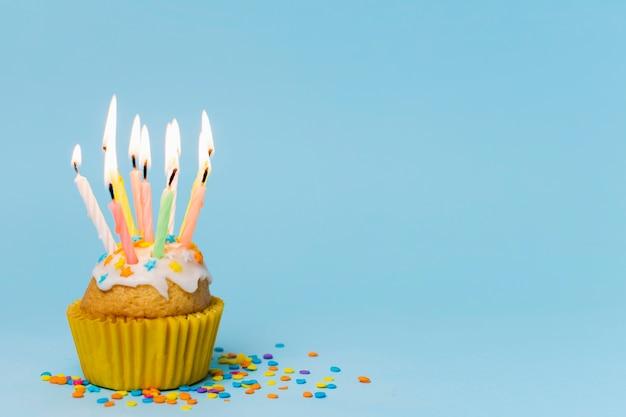 Petit gâteau avec des bougies allumées sur fond bleu avec espace de copie