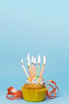Petit gâteau avec des bougies allumées et ruban