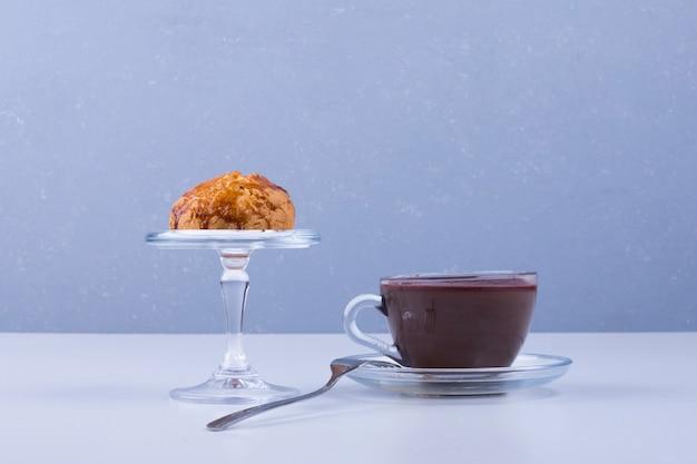 Un petit gâteau dans une tasse en verre servi avec du café