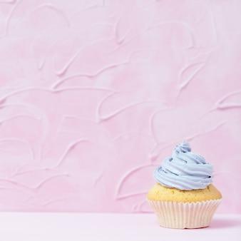 Petit gâteau décoré de crème au beurre violette sur fond rose pastel.