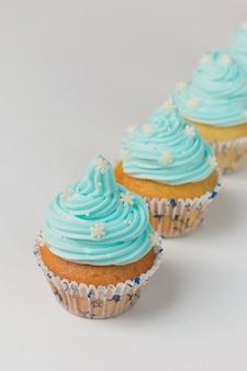 Petit gâteau décoré avec des flocons de neige au sucre et de la crème bleue. petits gâteaux d'hiver de noël