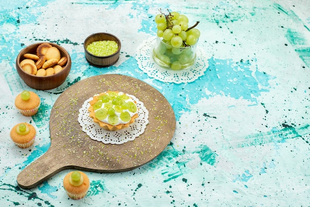 Petit gâteau avec une délicieuse crème et des biscuits de raisins verts tranchés et frais isolés sur un bureau bleu clair, gâteau sucré aux fruits