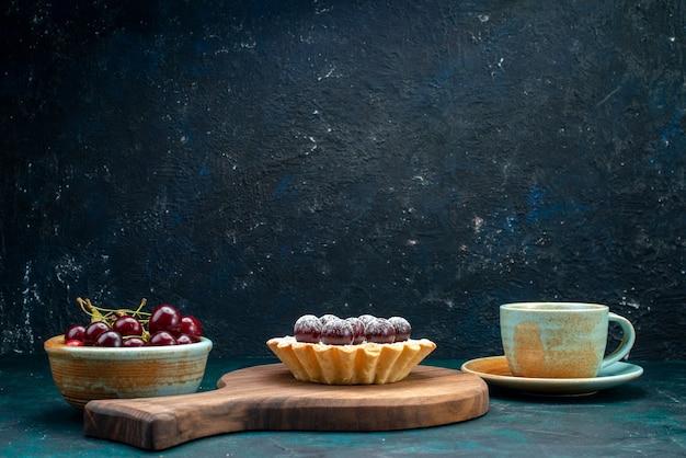 Petit gâteau avec de délicieuses cerises à côté du café et une assiette pleine de cerises