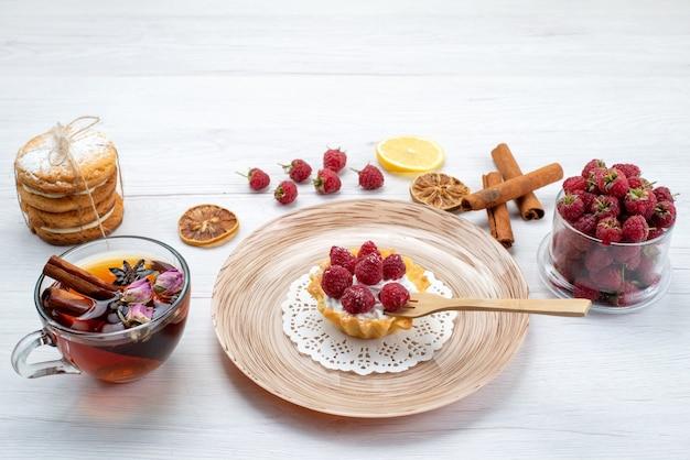 Petit gâteau délicieux avec de la crème et des framboises avec des biscuits sandwich thé à la cannelle sur blanc clair, biscuit gâteau aux fruits et baies