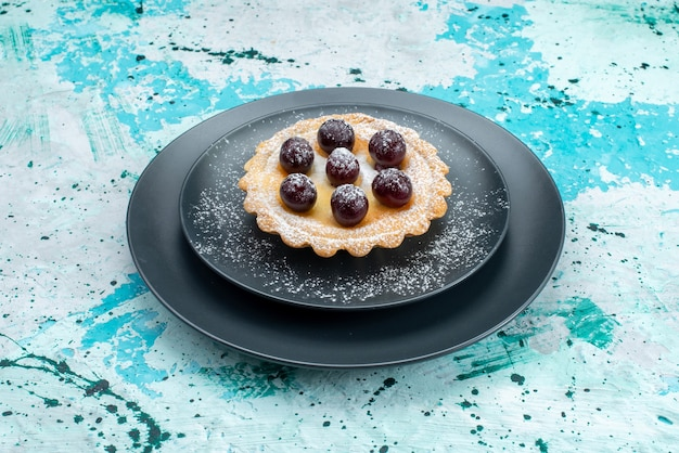 Petit gâteau avec du sucre en poudre et fruits sur bleu, thé sucré aux fruits à la crème de gâteau