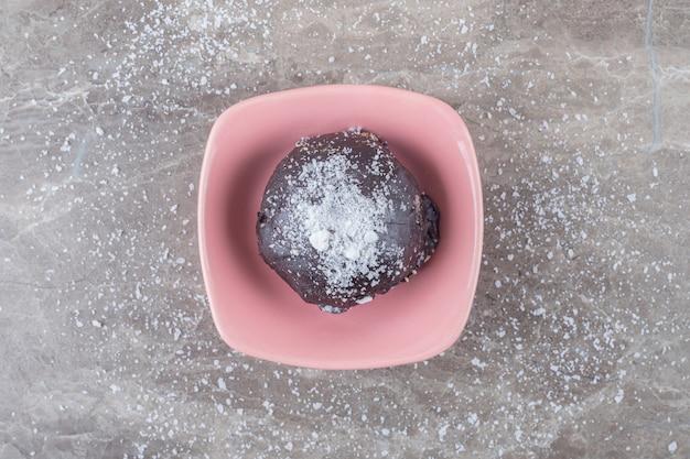 Petit gâteau enrobé de chocolat dans un bol sur une surface en marbre
