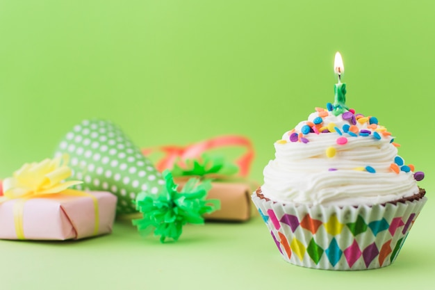 Petit gâteau frais avec une bougie illuminée sur une surface verte