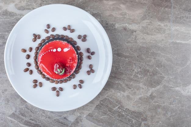 Petit gâteau, avec garniture au sirop de fraise et grains de café sur un plateau sur une surface en marbre