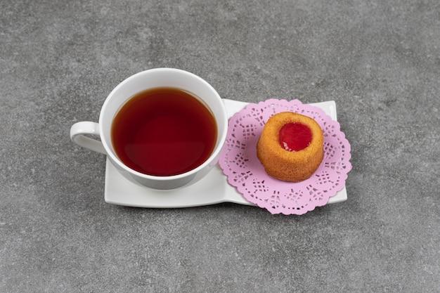 Petit gâteau avec de la gelée et une tasse de thé sur une surface en marbre