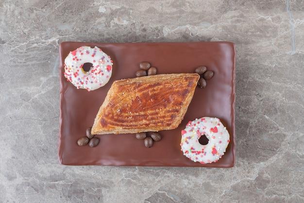 Petit gâteau, grains de café et beignets de la taille d'une bouchée sur un plateau sur une surface en marbre