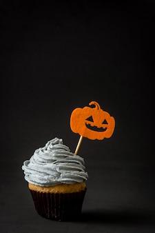 Petit gâteau d'halloween à la citrouille sur fond noir