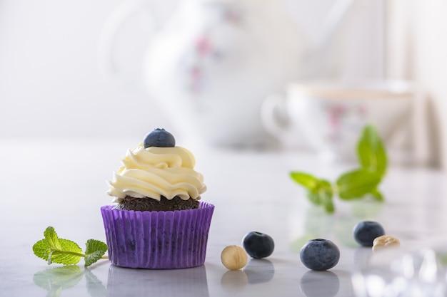 Petit gâteau à la myrtille et à la noisette dans un emballage violet sur un bureau en marbre naturel blanc.