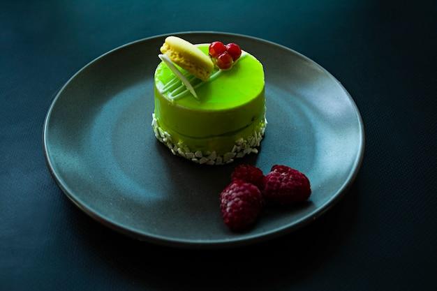 Un petit gâteau à la pistache avec un revêtement vert et décoré de viorne