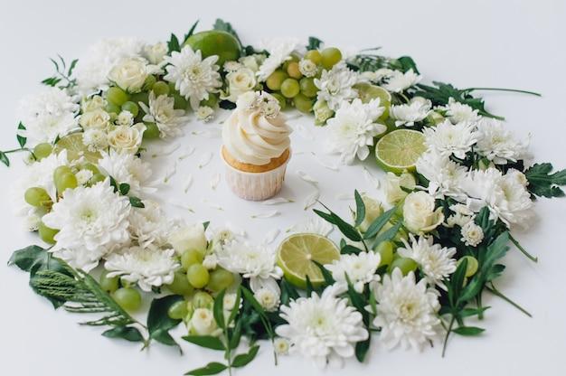Petit gâteau de printemps sur fond blanc avec des fleurs et des fruits